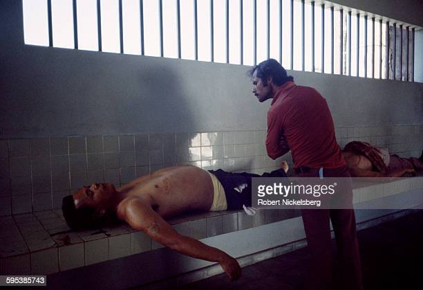 In the city morgue, an unidentified man looks at one of two corpses in the city morgue, La Libertad, El Salvador, August 10, 1984. Both victims were...