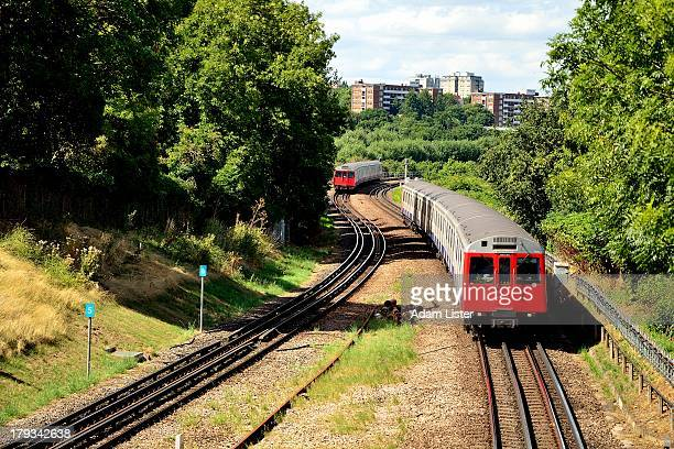 In the city suburbs, two iconic London Underground Tube Trains are seen passing each other on the tracks on a bright, sunny day. Approximately 55% of...