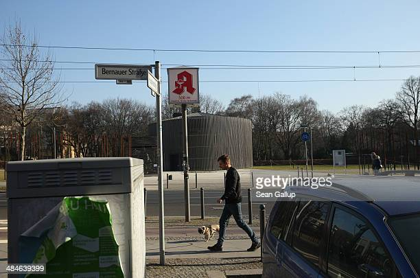 In the colour photo above a man walks a dog past the memorial to the Church of Reconciliation which was demolished by East Berlin authorities to make...