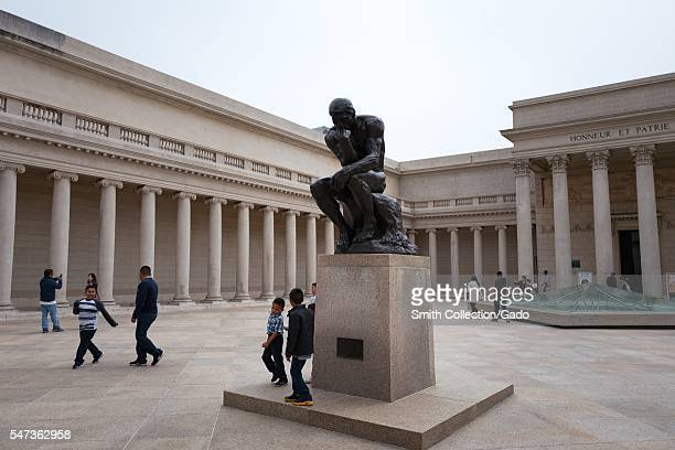 In the courtyard of the Legion of Honor art museum in the Lands End neighborhood of San Francisco children play near The Thinker a bronze statue by...