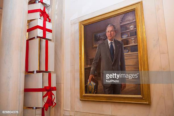 In the Cross Hall of the White House holiday decorations feature stacked columns of shiny presents next to the official portrait of George W Bush for...