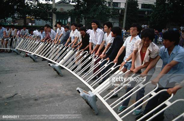 In the days after the military repression of the prodemocracy protests in Tiananmen Square Beijing residents tear down barricades put up to halt the...