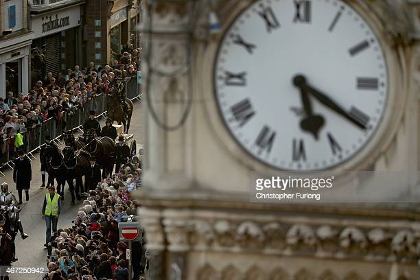 In the distance from a clock tower the coffin containing the remains of King Richard III is carried in procession past the memorial clock for...