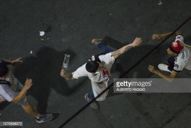 In the early morning a River Plate fan throws a bottle to the riot police at the Plaza de la Republica in Buenos Aires, Argentina after the team won...