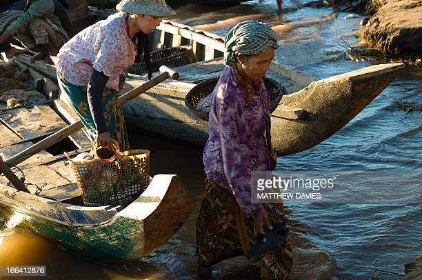 CONTENT] In The Early Morning Cambodian Fisher Women Disembark From Their Small Fishing Boats With Their Fish After Fishing In The River Kampong Cham...