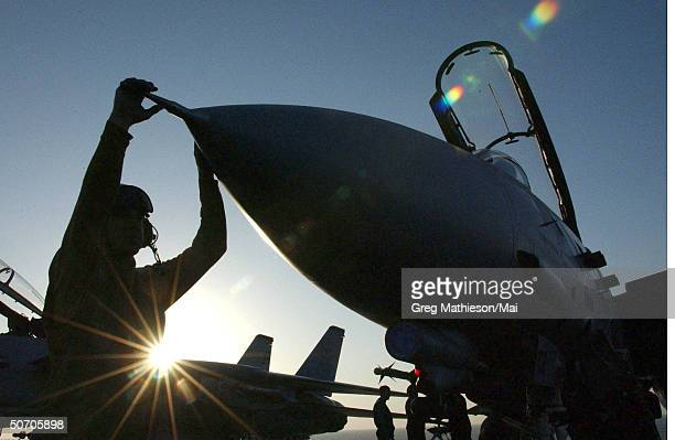 In the early morning light a Sailor securing an F14 Tomcat after completion of another night of flight operations and strike missions over...