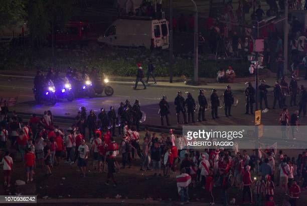 In the early morning riot police disperse River Plate fans at the Plaza de la Republica in Buenos Aires Argentina after the team won the allArgentine...