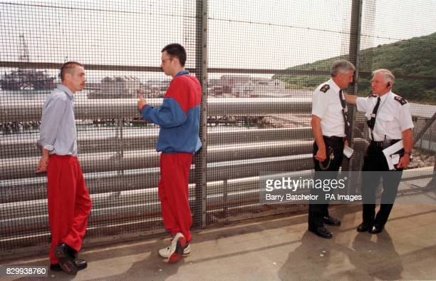 In the exercise yard aboard HM Prison Weare prisoners Nigel Harris from Wolverhampton Ron Koger from Lewisham with Prison Officers Tim O'Connor and...