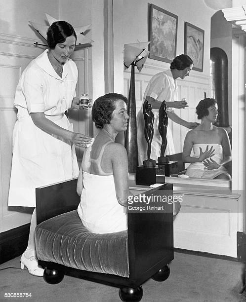 In the fashionable Gold Coast salon of Helena Rubinstein Carolyn Lang applies lotions to Billie Gloss' suntanned back bleaching it down so that Miss...