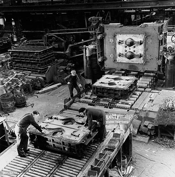 In the fettling shop at FH Lloyd box moulds separated showing exposed patterns between template behind workers which has just made an impression of...