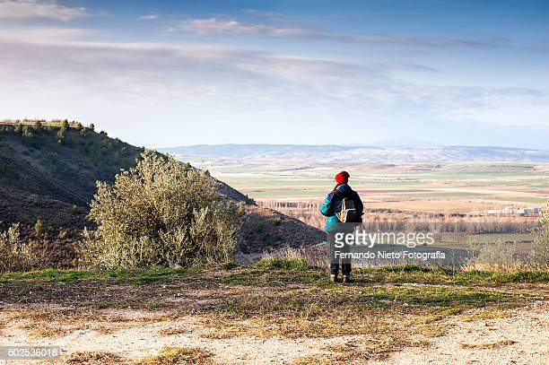 In the field, a hiker is contemplating the landscape from a lookout at a high place