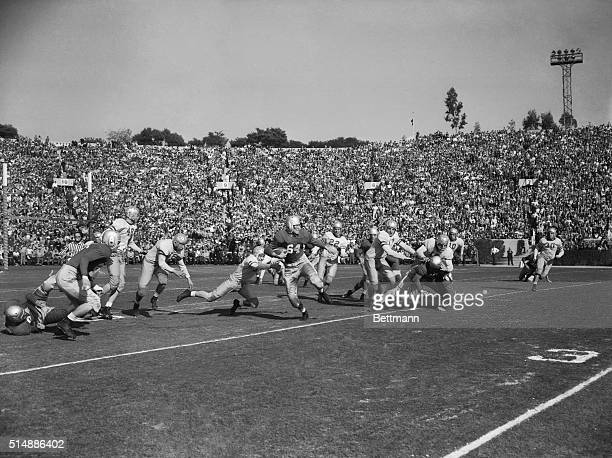 In the first play of the Rose Bowl Game Georgia halfback Lamar Davis eludes UCLA end Herb Wiener and halfback Ev Riddle to return UCLA's kickoff for...