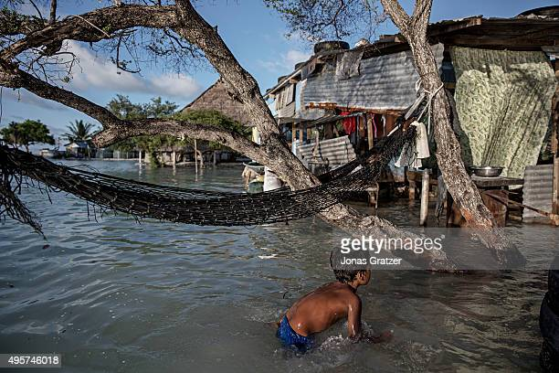 In the flooded village Eita a young boy is swimming outside his house in the sea water The people of Kiribati are under pressure to relocate due to...