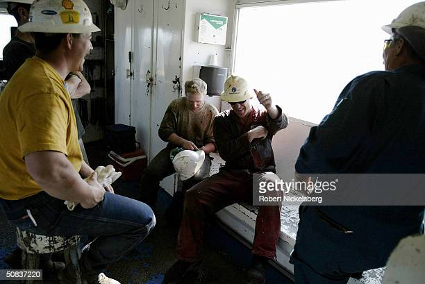 In the floor cabin of a natural gas drilling rig the driller and his crew of roughnecks exchange stories at the end of their 12hour shift May 8 2004...