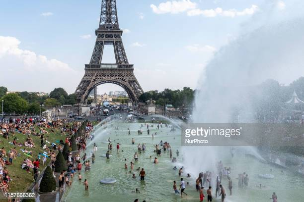 In the foreground are the powerful water jets of the Fontaine du Trocadéro under which Parisians cool off with the Eiffel Tower in the background...