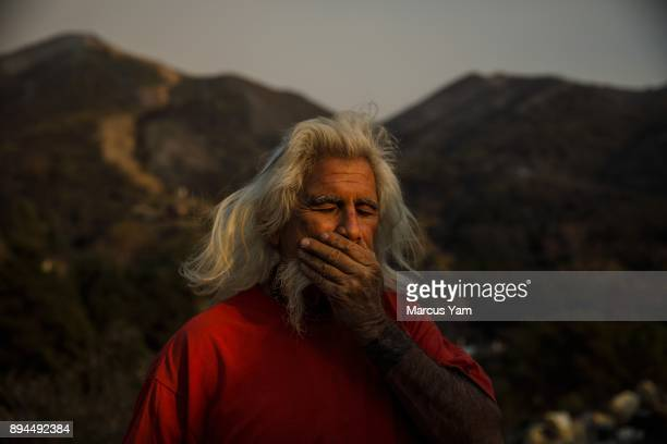 In the foreground of the ridges that were burned by the Thomas Fire Rusty Smith stands outside his home that survived the flames that were kicked up...