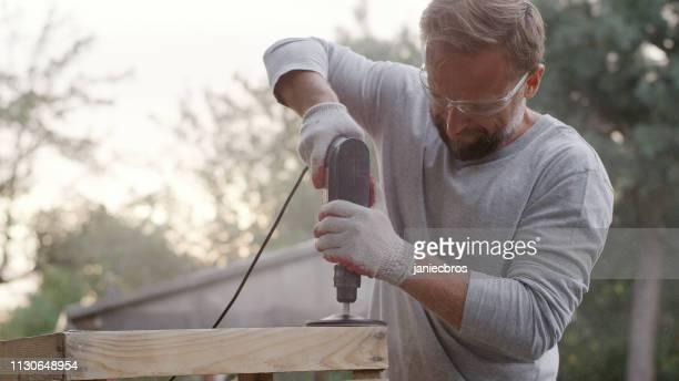 diy in de tuin. renoveren van oude houten meubelen - molen stockfoto's en -beelden