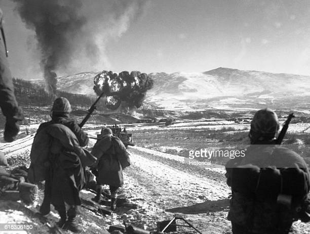 In the Hagaruri area of Korea in December US Marines move forward after effective closeair support flushes out the enemy from their hillside...