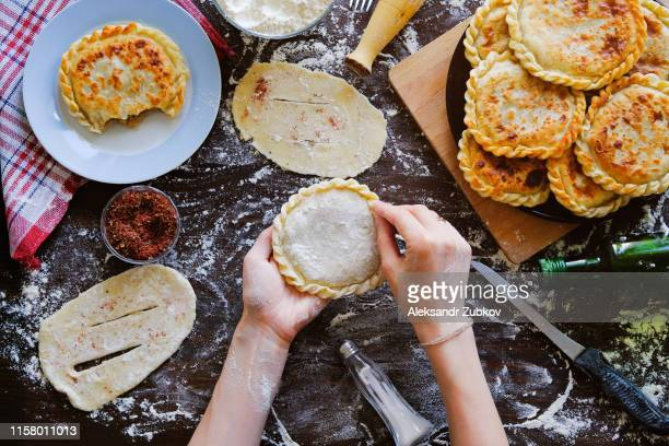 in the hands of the cook georgian flat cake of raw dough on the background of a wooden table, sprinkled with flour. a woman cooks a pie or khachapuri. near food, kitchen utensils. home life. - georgian culture stock pictures, royalty-free photos & images