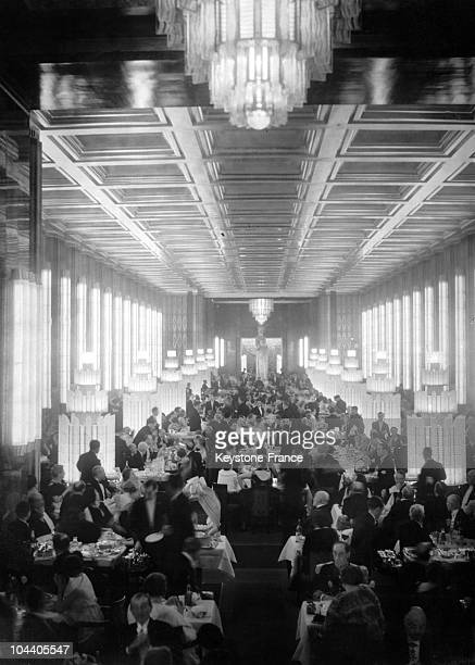 In the harbour of Le Havre the dining room of the transatlantic liner the NORMANDIE greeting a crowd of famous figures including the President of the...