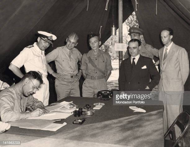 In the headquarters tent the diplomatic and military authorities are signing the armistice between Italy and the Alllied Forces From the left the US...