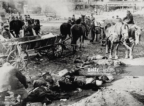 In the heap of rubble of the city centre some soldiers unload from two carts the bodies of some victims of the violent bombing of the allied forces...