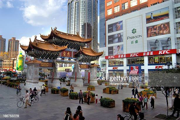 In the heart if the city of Kunming capital of Yunnan a modern western style shopping place side with the local architecture of a traditional gate