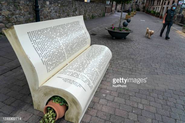 In the heart of the historic center of Cartes, Cantabria, Spain, on June 6, 2021 there is a bench in the shape of a book, specifically a simulated...