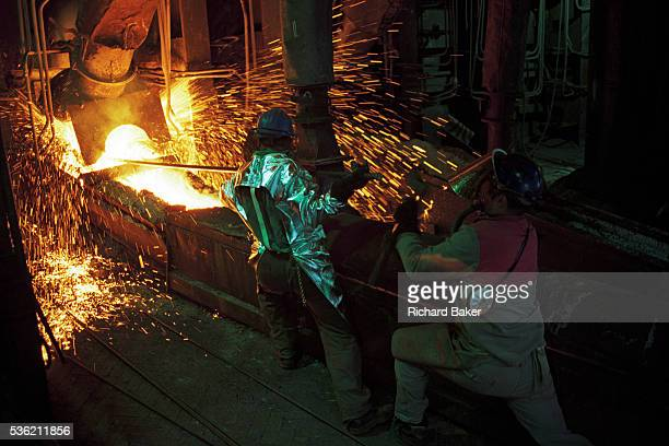 In the heat dust and sparks of a postcommunist industrial mill we see two Bulgarian copper manufacturing workers wearing heatproof suits and helmets...