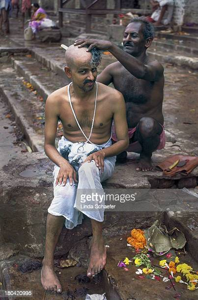 CONTENT] In the Hindu tradition a son has his hair shaved before the funeral of his father This is at a bathing ghat near the crematorium where the...