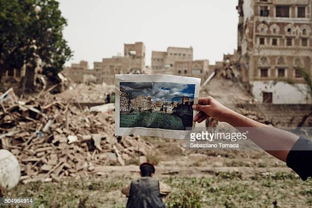 In the historical old city of Sana'a civilians local response teams and Houthi fighters clear the rubble of four houses that were destroyed by what...