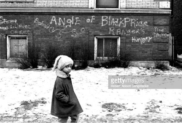 In the inner city a young girl walks past a graffitied wall bearing various words and phrases among them 'Angle of Black Pride' 'Hungry' and 'The...