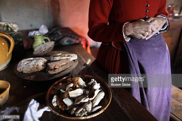 In the Isaac Allerton house Sara Godbertson stands next to a table with turkey for turkey fricassee breads butter and pepper corn Roleplayers and...