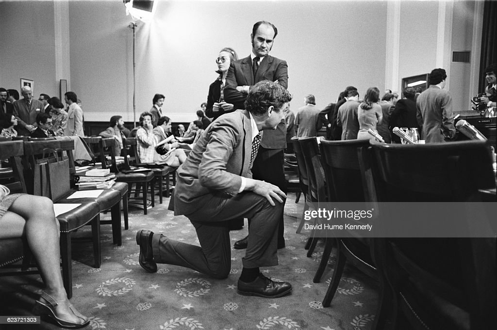 In the Judiciary Committee hearing room on Capitol hill, Hillary Rodham (centre, left, before she married Bill Clinton), working as a lawyer for the Rodino Committee, which was bringing impeachment charges against President Richard Nixon, Washington DC, April 25, 1974. Kneeling in the foreground is John Doar, special counsel for the House Judiciary Committee.