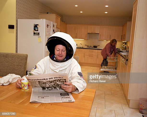 In the kitchen on a Sunday morning spacesuited frequent flyer astronaut Alan Watts reads the Sunday newspaper while his wife empties the dishwasher...