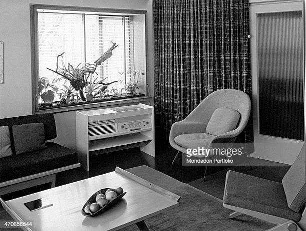 'In the living room of a flat stylishly furnished with a sofa a small table with fruit bowl an awning and a window with shutters and ornamental...