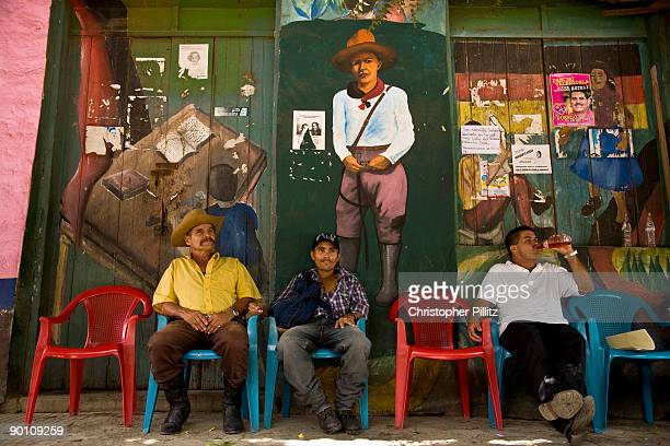 In the main square of Jinotega town people rest drink or eat at a street snack stop against a revolutionary mural depicting Agusto Sandino and Che...
