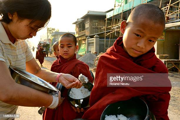 In the main street of Nyaung Shwe near the Inlay Lake a woman giving freshly cooked rice to very young monks as they do their round to collect alms...