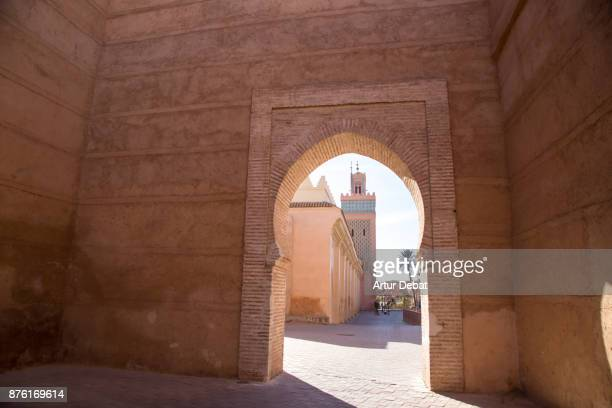 In the Marrakech medina with nice salmon colors, composition of the mosque minaret inside the wall gate with nice colors and geometries.