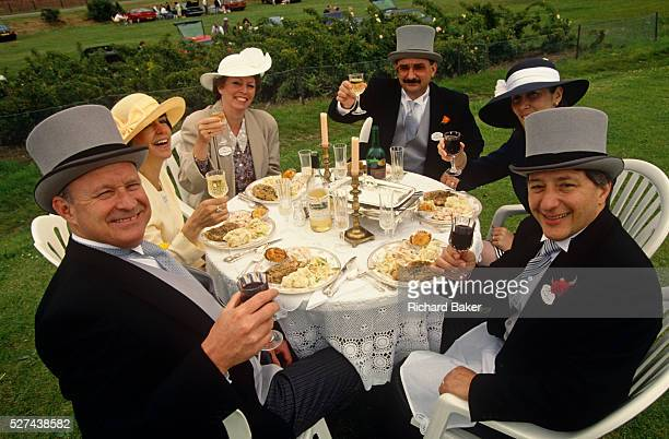In the middle of a field serving as a grass car park, three couples celebrate the Ladies' Day event at Royal Ascot. Holding their glasses to toast a...