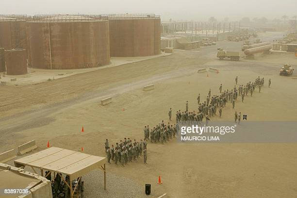 In the middle of a sandstorm US troops of 3rd Battalion 187th Infantry Regiment stand to attention as they listen to their national anthem during a...