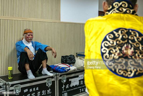 In the middle of stage performance an old actor rests on prop box at backstage Peking opera or Beijing opera is a form of traditional Chinese theater...