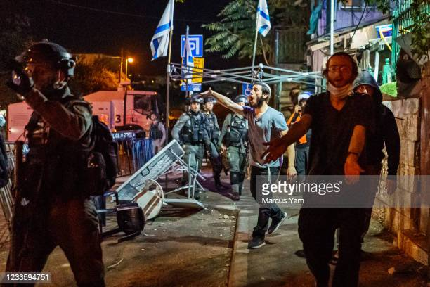 In the midst of the unrest, Jewish settlers argue with local Palestinians as the Israeli police officers separate the crowds in the Sheikh Jarrah...