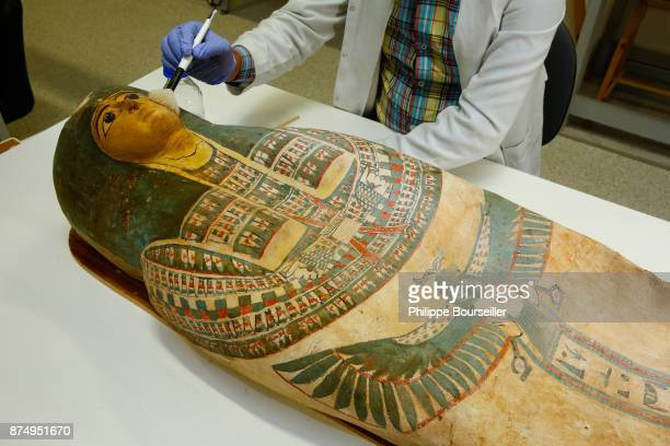 In the mummy restoration laboratory of the GEM in Cairo the curator Sayed Gomaa delicately brushes the sarcophagus of a mummy from Beni Souf