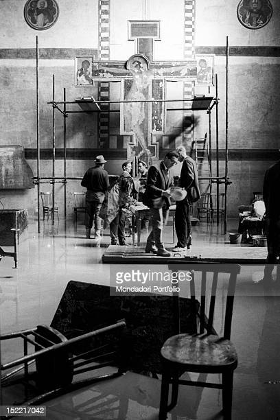 In the Museo dell'Opera of Santa Croce workers and restorers immediately at work to restore Cimabue's 'Crucifix' to its former beauty a work of art...