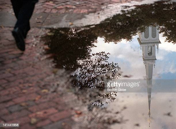 In the North End a man walks by a puddle with the reflection of the Old North Church