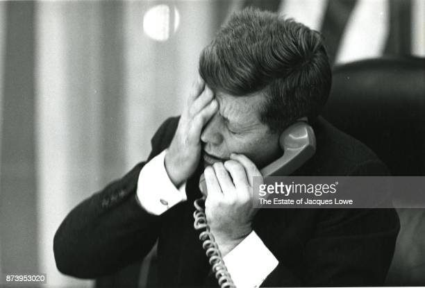 In the Oval Office US President John F Kennedy holds his hand to his head as he is informed via telephone of Patrice Lumumba's assassination...