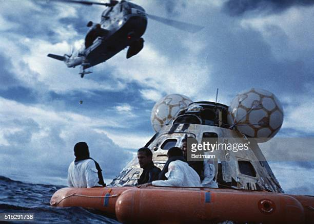 In the Pacific Ocean Astronauts from Apollo 13 Fred Haise John Swigert and James Lovell all in white suits await a helicopter pickup With them in the...