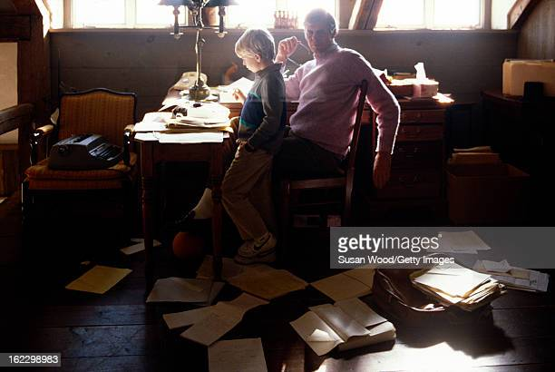 In the paper-strewn writing studio at his summer home, American writer and journalist George Plimpton at his desk with his son, Taylor Ames Plimpton,...