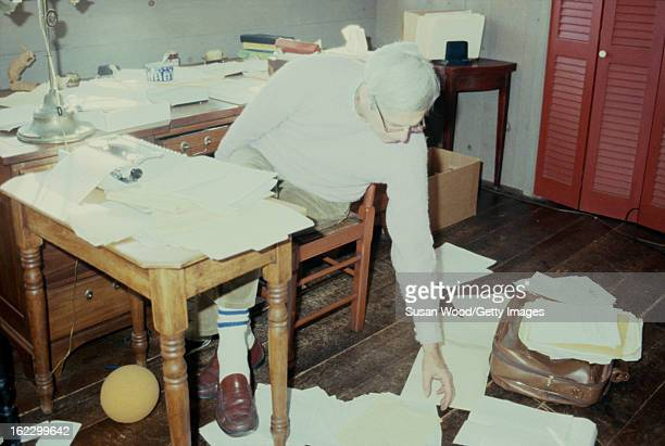 In the paper-strewn writing studio at his summer home, American writer and journalist George Plimpton works at his desk, Wainscott, New York, January...